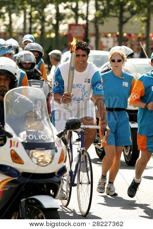 BARCELONA - JUNE 28: Spanish cyclist Miguel Indurain carries the Athens 2004 Olympic torch during the Barcelona Torch Route through the city streets, June 28, 2004 in Barcelona, Spain