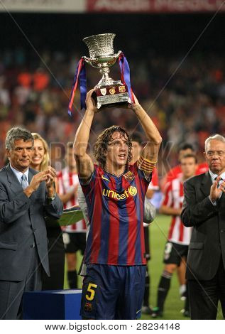 BARCELONA, SPAIN - AUG. 23: Barcelona's Carles Puyol holds up the spanish Super cup after the match between Barcelona vs Athletic Bilbao at the New Camp Stadium in Barcelona on August 23, 2009.