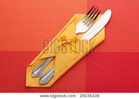 Fork and knife in a yellow cloth with a bow on a red tablecloth