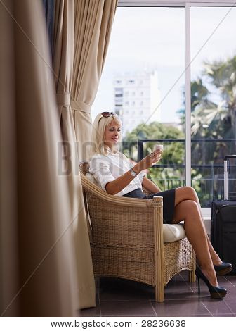 Businesswoman Using Mobile Phone In Hotel Room