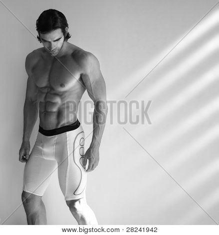 Sexy black and white portrait of young muscular male fitness model in underwear with window light streaming in