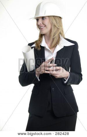 Lady Architect Holding Blue Prints Wearing A White Hard Hat