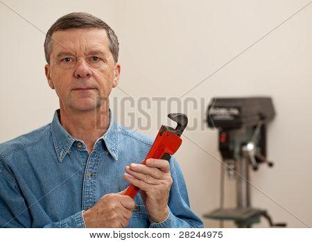 Senior Man Holding A Large Wrench