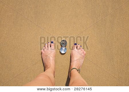 Compass Between Woman Feet