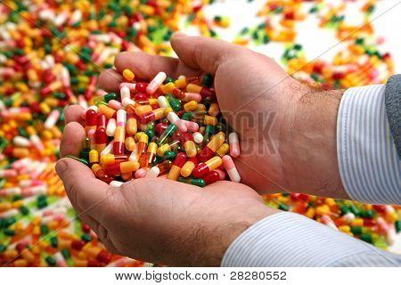 Hands full of medication pill capsules
