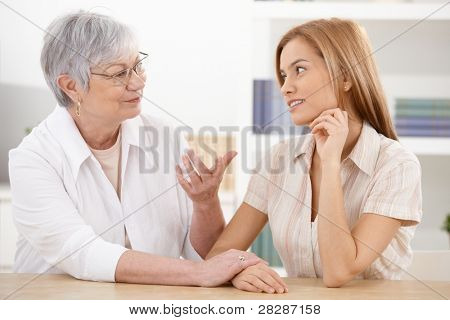 Young woman visiting grandmother at home, chatting, smiling.?