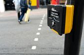 Close Up Of Yellow Metal Crosswalk Button For Pedestrian Crossing Signal In London, Uk For Traffic R poster
