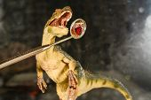 Dinosaur Velociraptor Looks At The Teeth In A Dental Mirror. The Concept Of Dental Care. Toy Dinosau poster