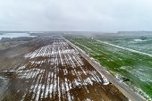 Green Field With Winter Crops And Plowed Field. Fields Covered With Snow. Aerial View. poster