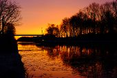 Dramatic And Colorful Sunrise Over A Beautiful Early Winter Landscape With A Frozen River Or Canal,  poster