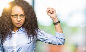 Young beautiful business girl with curly hair wearing glasses angry and mad raising fist frustrated  poster