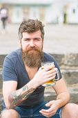 Hipster With Long Beard Looks Relaxed. Bearded Hipster Holds Beer Mug, Drinks Beer Outdoor. Craft Be poster