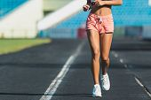 Sport. Athletic Young Woman In White Sneakers Run On Running Track Stadium. Close-up On Sports Shoes poster