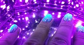 Nail Care And Manicure Concept. Closeup New Nail Polish On Clients Nails In Ultraviolet Lamp. Woman  poster