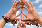 youth culture, gesture and people concept - close up of hippie friends showing peace hand sign over  poster