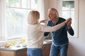 Loving Senior Couple Husband And Wife Dancing In The Kitchen poster