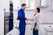 Male Pest Control Worker Shaking Hands With Happy Woman In Kitchen poster