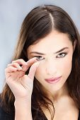 picture of contact lenses  - Young woman holding contact lens with two fingers in front of her eye - JPG
