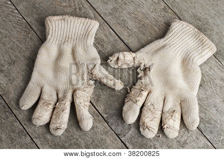 Old Cotton Work Gloves On Weathered Wood.