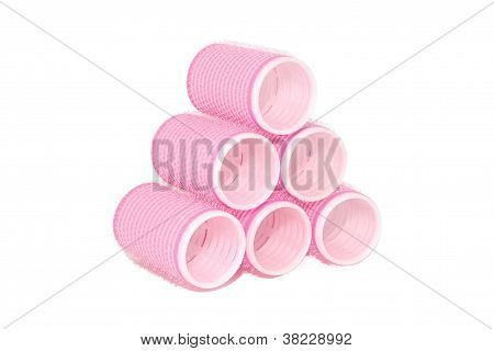 Six pink velcro rollers stacked in a pyramid