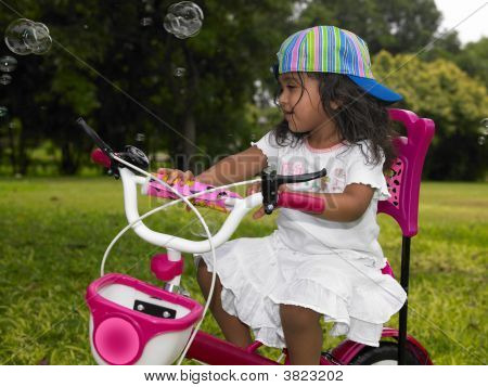 Asian Girl In The Garden Riding Her Cycle