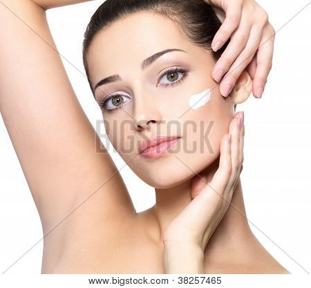 Beauty Face Of Young Woman With Cosmetic Cream On A Cheek.