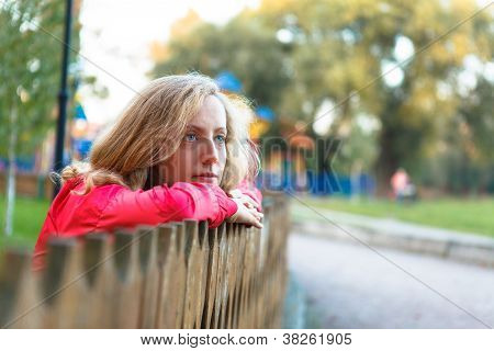 Young Woman Relaxation Leaning On A Wooden Fence