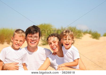 Family Of Four Portrait On Sandy Coast