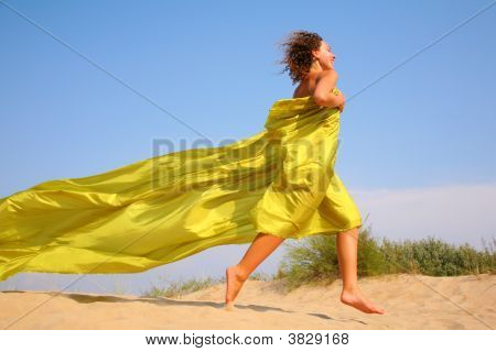 Young Girl Runs On Sand In Yellow Fabric Shawl