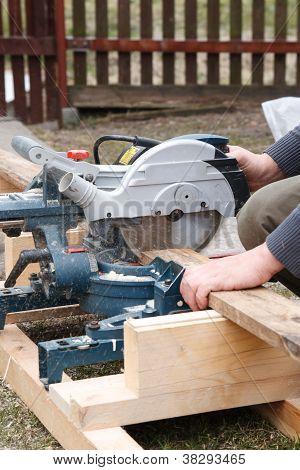 Carpenter Sawing Plank