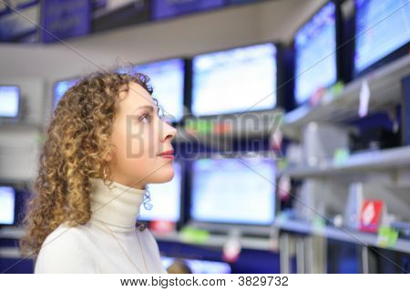 Young Woman Looks At Tvs In Shop