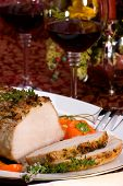 stock photo of christmas dinner  - Delicious sliced garlic thyme roast pork loin and glass of red wine ready for Christmas dinner on holiday table.