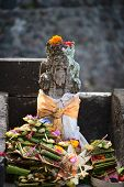foto of customary  - Typical outdoor Balinese Hindu statue with a lot of offerings - JPG