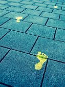 stock photo of painted toes  - Yellow paint footprints on sidewalk symbolize progress - JPG