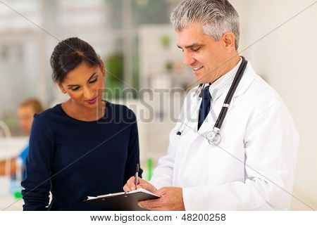 senior doctor checking young patient's test result