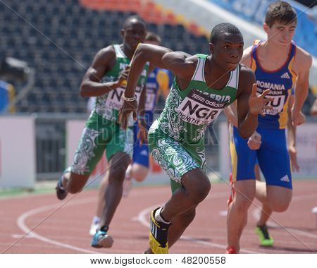DONETSK, UKRAINE - JULY 13: Oduduru (in front) and Atuma, both of Nigeria, compete in the boys medley relay during World Youth Championships in Donetsk, Ukraine on July 13, 2013. Right: Radu, Romania