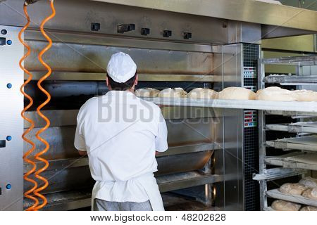 Male baker baking fresh bread in the bakehouse