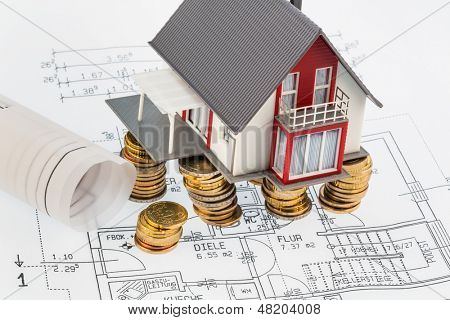a house stands on geldm,�?�?�?�£ coins and a blueprint. photo icon for building societies
