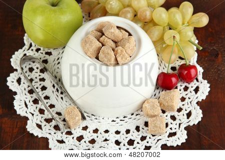 Unrefined sugar in white sugar bowl on wooden background