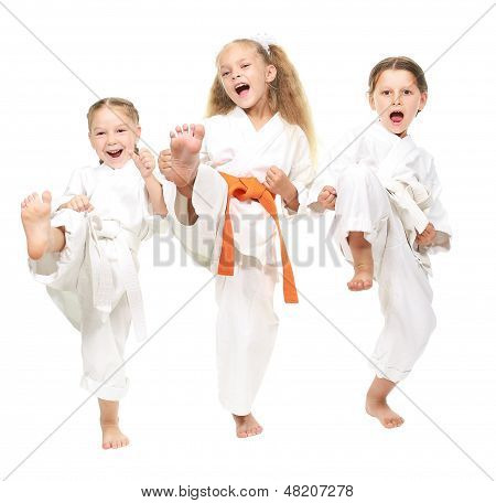 Three cheerful girl dressed in a white kimono kick leg