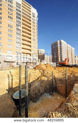Pit for sewerage with dirty water near high multi-storey yellow building under construction at sunny day.