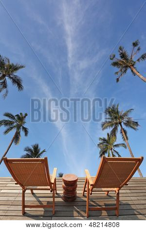 The excellent overview of the blue sky, white clouds and swaying palm trees. Two convenient comfortable guest sun loungers and a bedside table are worth on a wooden platform