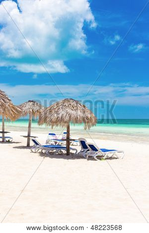 Guarda-chuvas numa praia tropical no Coco Key (Cayo Coco) em Cuba (em um dia de verão ensolarado lindo)