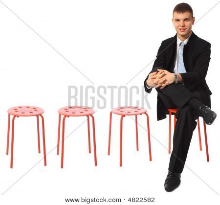 Young Businessman Sits On Red Stool Leg On Leg