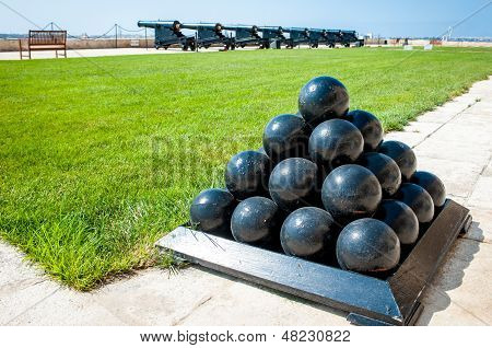 Old Cannonballs Stacked In Pyramid, In Front Of Cannons, On Valletta Castle, Malta