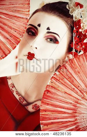 Art portrait of a stylized Japanese geisha with fan. Body painting project.