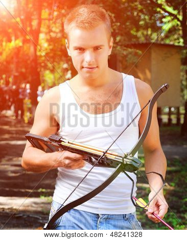 young man with a crossbow and arrows in the woods