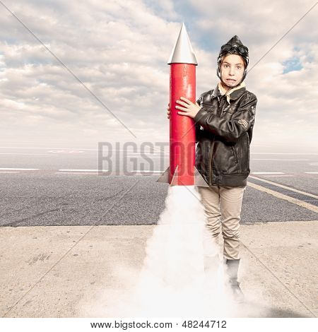 little aviator holding a rocket at the airport