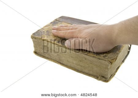 Male Hand On The Vintage Bible Isolated Over White