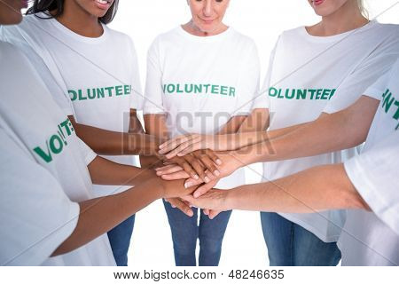 Group of female volunteers with hands together on white background